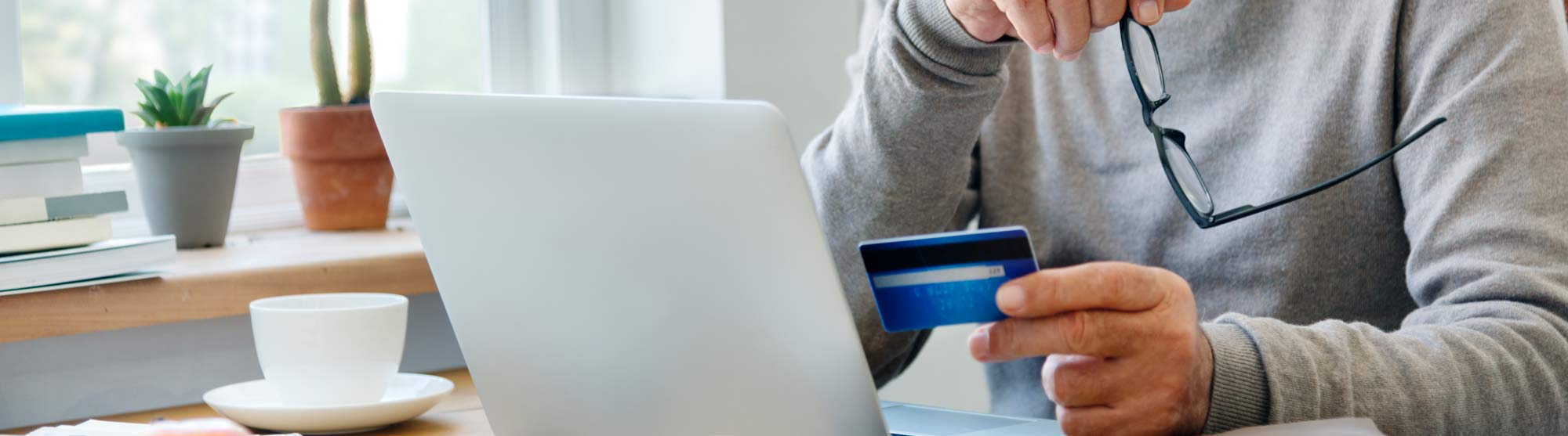 Older man using credit card for online shopping